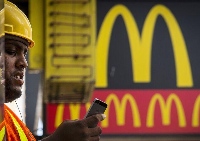 Cliente olha para celular perto de um McDonald's em Nova York, 23 de julho de 2015