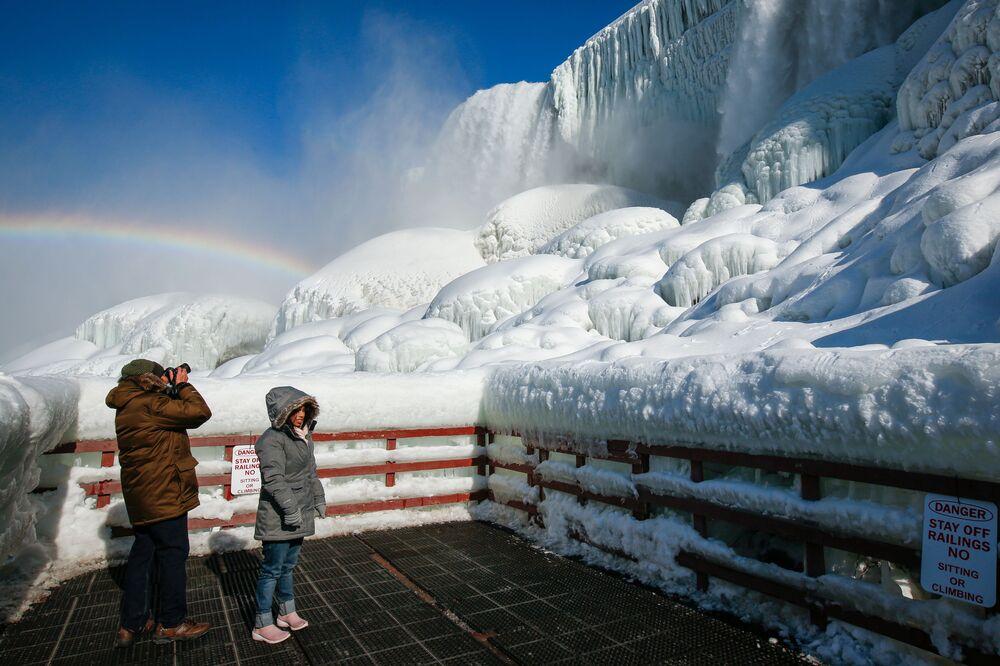 Visitantes em meio ao arco-íris sobre o gelo na base das cataratas do Niágara, Nova York, EUA, 21 de fevereiro de 2021