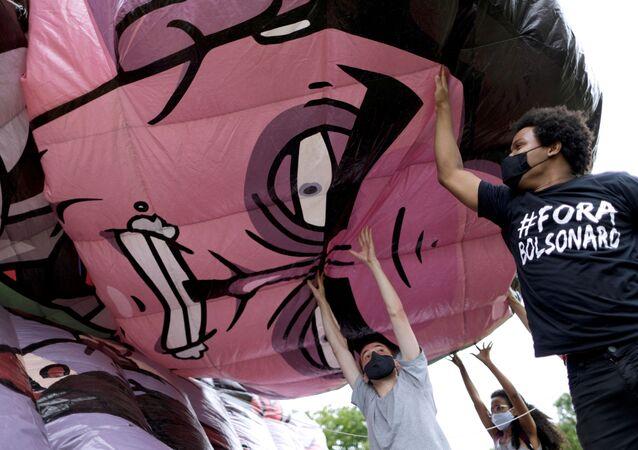 Ativistas e membros de organizações sociais inflando um boneco representando o presidente do Brasil, Jair Bolsonaro, 21 de fevereiro de 2021