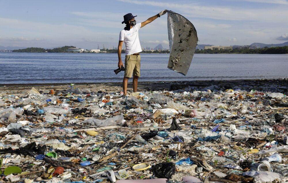 Fotógrafo e biólogo marinho Ricardo Gomes, membro do Instituto Mar Urbano, organização não governamental, pega lixo nas margens da Baía de Guanabara no Rio de Janeiro, 24 de fevereiro de 2021