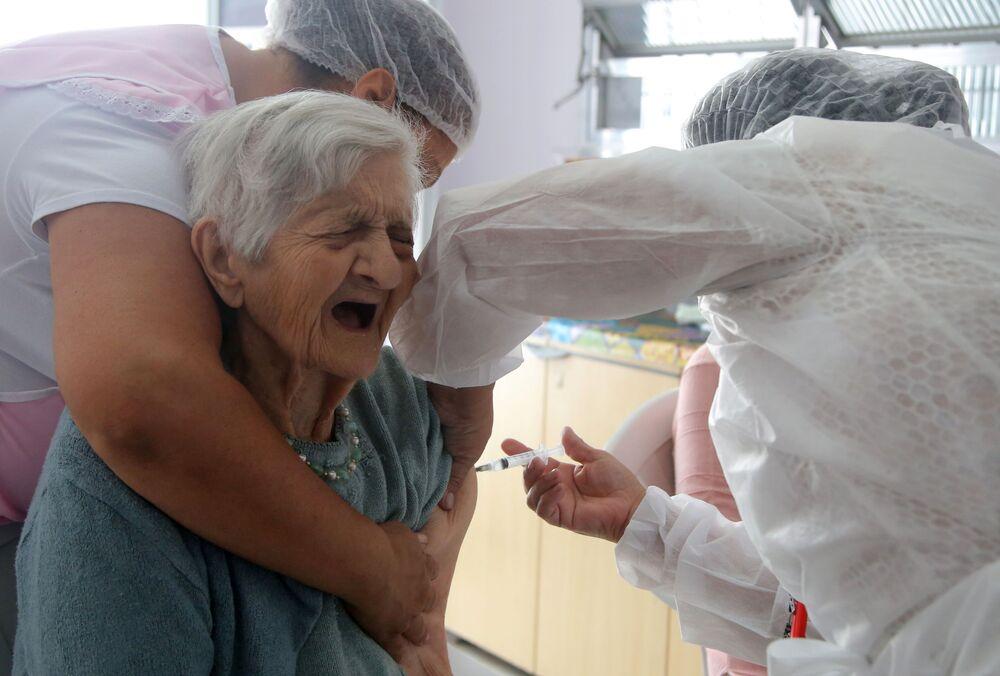 Funcionária da saúde aplica segunda dose da vacina CoronaVac a uma pessoa idosa na Residencial e Creche para Idosos Solar das Acácias perto de São Paulo, Brasil, 26 de fevereiro de 2021