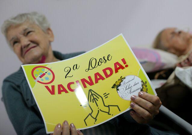 Senhora comemora após receber a segunda dose de vacina contra a COVID-19, em casa de repouso de Guarulhos (SP), 26 de fevereiro de 2021
