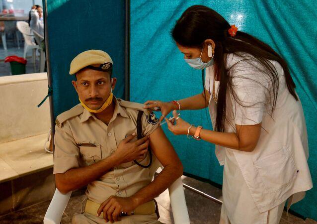Policial indiano recebendo dose da vacina COVISHIELD, fabricada pelo Instituto Serum da Índia