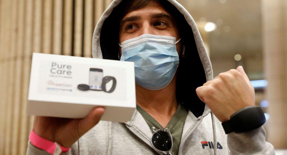 Após pousar em Israel, viajante mostra pulseira eletrônica para rastreamento da COVID-19, no Aeroporto Internacional Ben Gurion