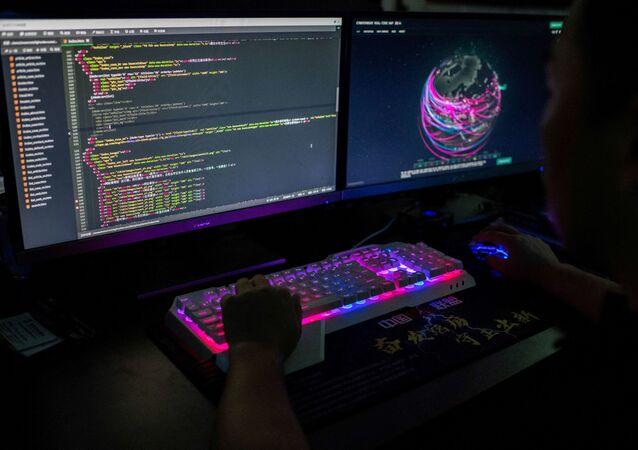 Um membro do grupo de hackers usando um site que monitora ataques cibernéticos globais em seu computador
