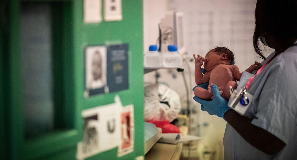 Enfermeira segura recém-nascido, durante a pandemia do coronavírus, em maternidade de Paris, França, 17 de novembro de 2020