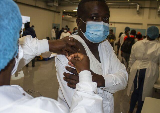 Enfermeiro recebe dose da vacina de Oxford/AstraZeneca, entregue pelo consórcio COVAX, em Luanda, no dia 2 de março de 2021