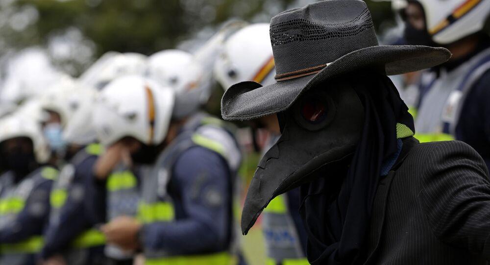 Manifestante usa máscara de pássaro preto, simbolizando a peste negra, em Brasília, 1º de março de 2021