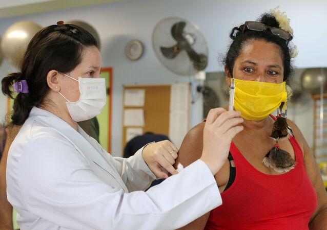 Mulher indígena observa segunda dose da vacina CoronaVac contra o SARS-CoV-2 em uma unidade de saúde de Guarulhos, São Paulo, Brasil, 2 de março de 2021