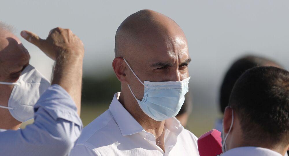 Em Luque, o então ministro da Saúde do Paraguai, Julio Mazzoleni, conversa durante a chegada de vacinas Sputnik V contra a COVID-19, em 18 de fevereiro de 2020