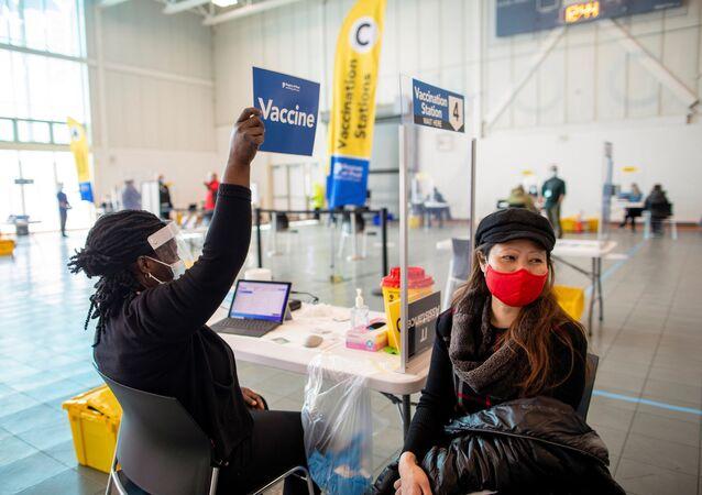 Enfermeira se prepara para vacinar mulher com dose da Moderna em Ontario, no Canadá