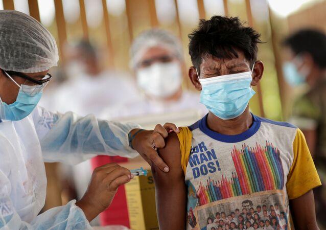 Homem da etnina indígena Hupda recebe dose da vacina contra o coronavírus de Oxford/AstraZeneca na aldeia Taracua Igarapé, no município de São Gabriel da Cachoeira, no Amazonas