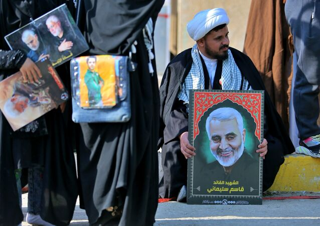 Apoiadores das Forças de Mobilização Popular assistem a procissão de aniversário do assassinato de Abu Mahdi al-Muhandis, com fotos dele e de Qassem Soleimani, em Najaf, Iraque, 4 de janeiro de 2021