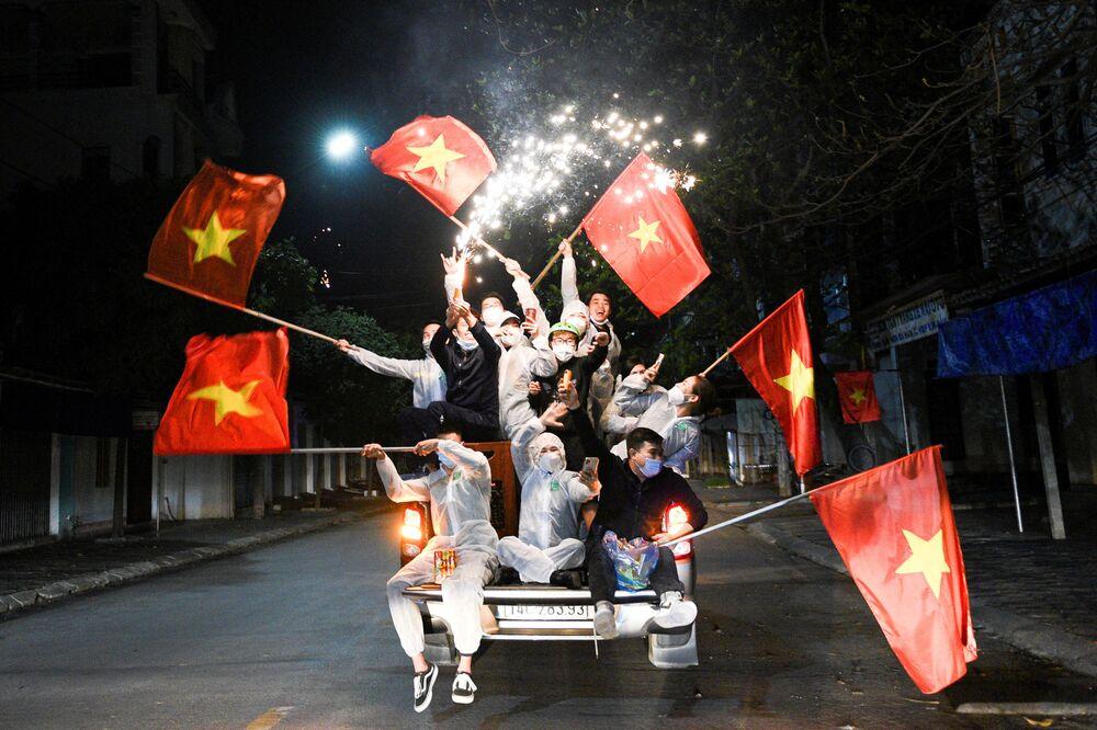 Residentes saindo às ruas para celebrar com bandeiras nacionais e fogos de artifício após o cancelamento do distanciamento social na cidade Chi Linh, Vietnã, 3 de março de 2021