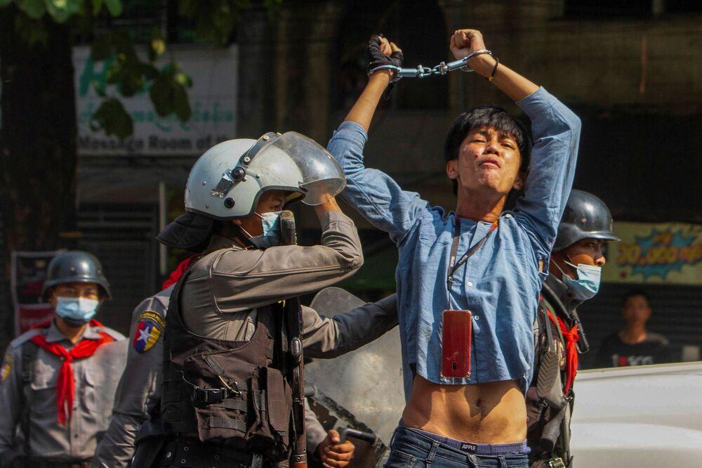 Manifestante detido por policiais durante protestos contra golpe militar em Myanmar, 27 de fevereiro de 2021