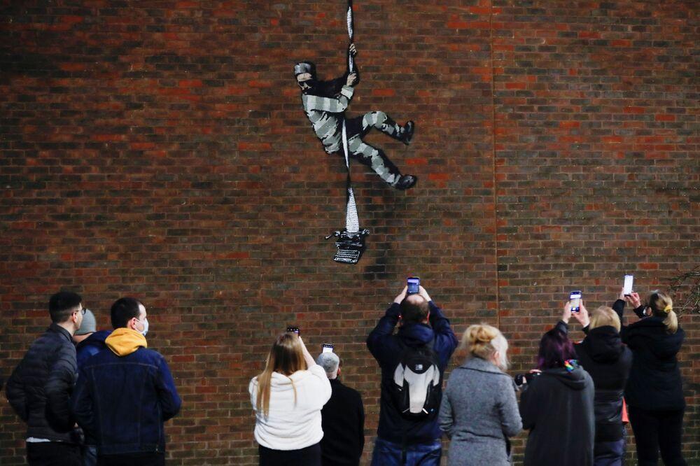 Pessoas tirando fotos perto de novo grafite em um muro, feito alegadamente por Banksy, Reino Unido, 1º de março de 2021