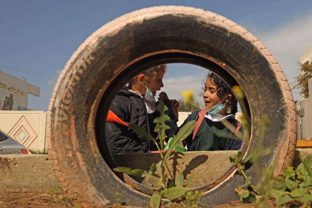 Estudantes palestinos aguardam ônibus escolar, cidade de Gaza, 3 de março de 2021