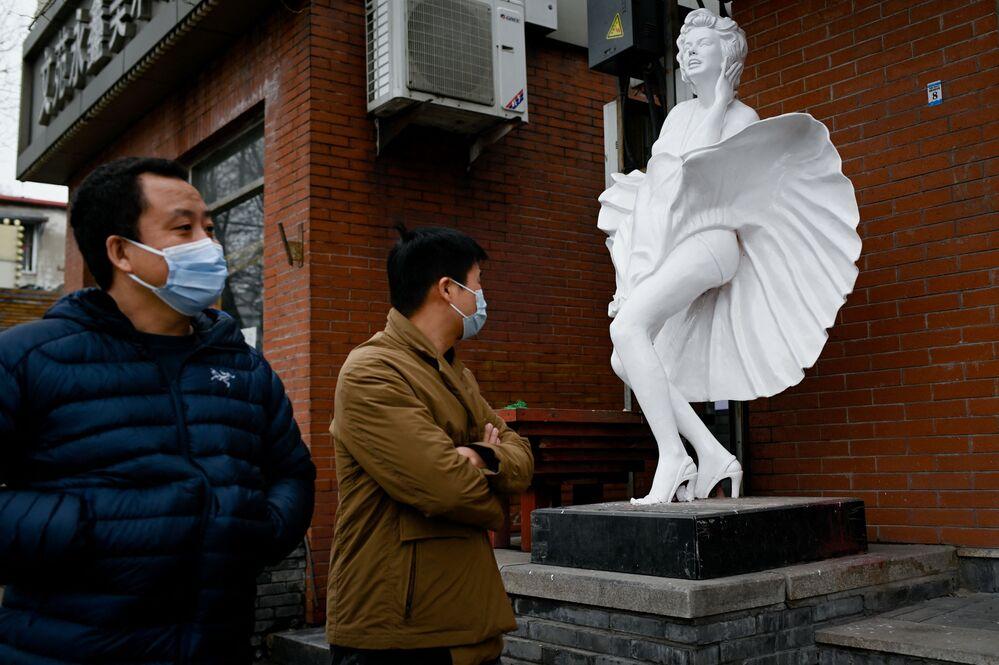 Transeuntes perto de estátua ao lado de uma loja em Pequim, China, 2 de março de 2021