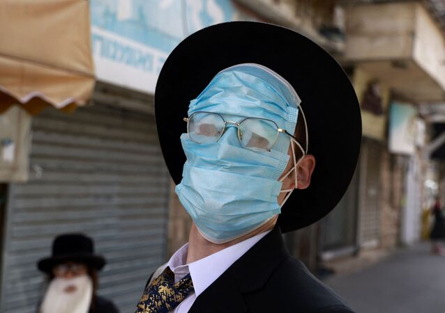 Homem usa várias máscaras durante celebrações de Purim, Jerusalém, 28 de fevereiro de 2021