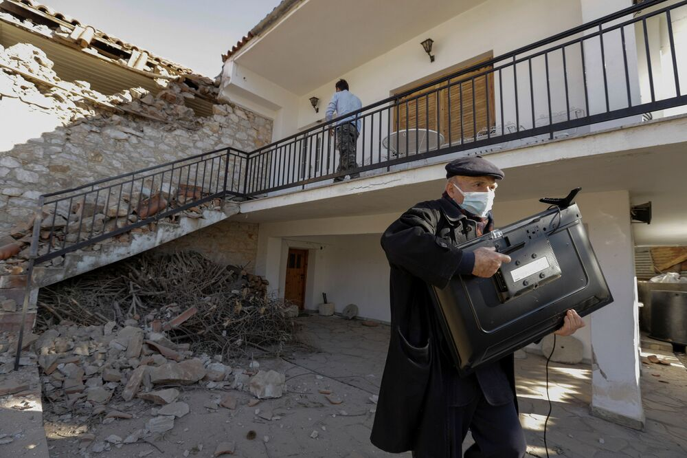 Homem levando televisão de sua casa destruída por terremoto na Grécia central, 3 de março de 2021