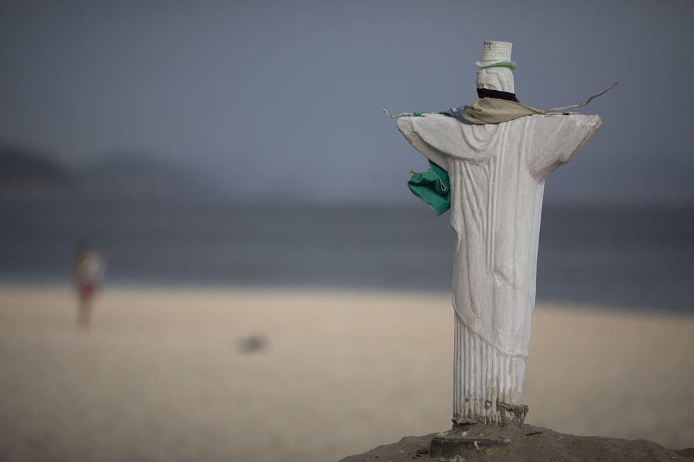 Réplica da estátua de Cristo Redentor usando máscara facial na praia de Copacabana após entrada em vigor de novas medias de contenção da COVID-19, 5 de março de 2021, Rio de Janeiro