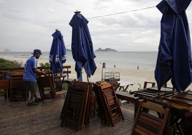 Funcionário empilha cadeiras e mesas em um bar depois de o prefeito Eduardo Paes anunciar novas medidas para combater COVID-19, Rio de Janeiro, 5 de março de 2021