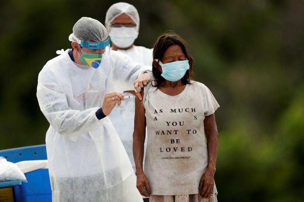 Indígena sendo vacinada contra a COVID-19 com o imunizante Sinovac na aldeia de Santo Atanásio, Amazonas, 3 de março de 2021