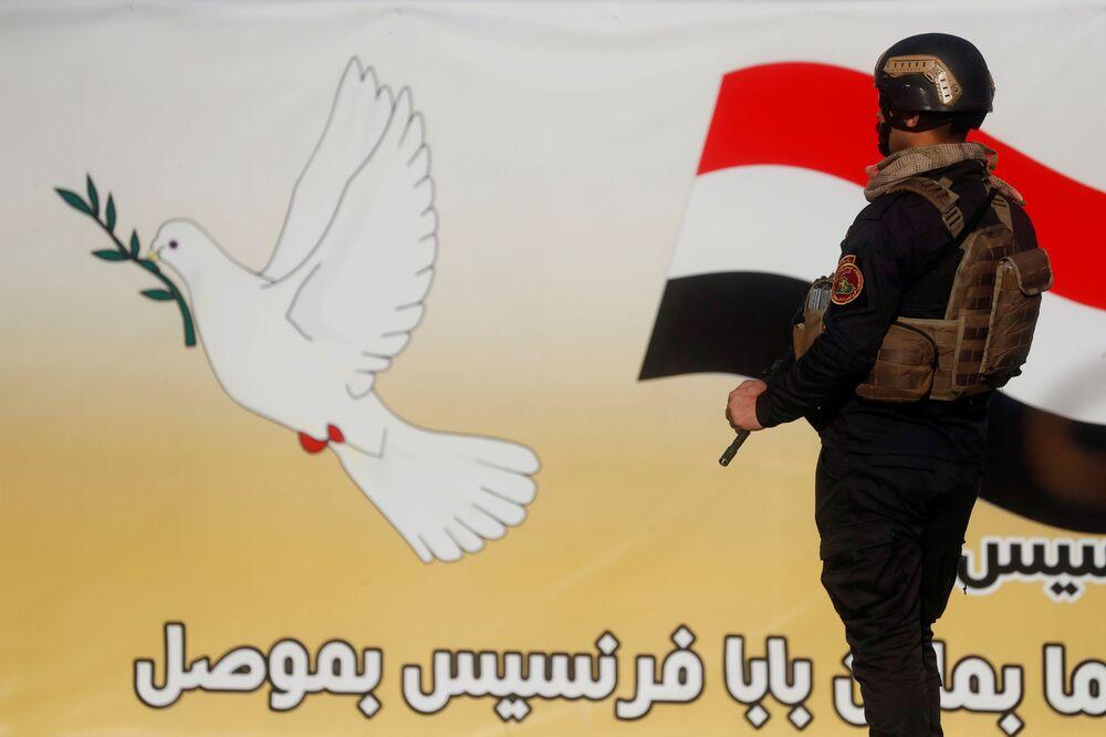 Um agente de segurança vigia a área antes da chegada do Papa Francisco a Mossul, Iraque