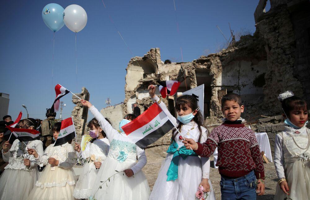 Crianças segurando bandeiras aguardam a chegada do Papa Francisco em Mossul