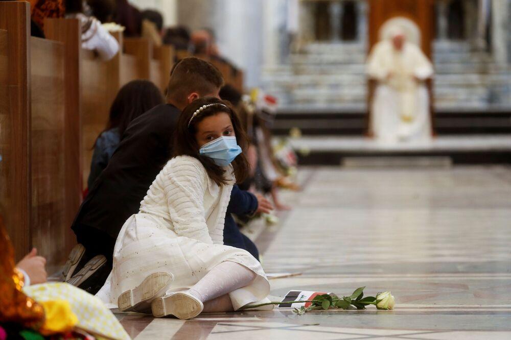 Menina no chão da igreja durante missa do Papa Francisco na cidade de Qaraqosh