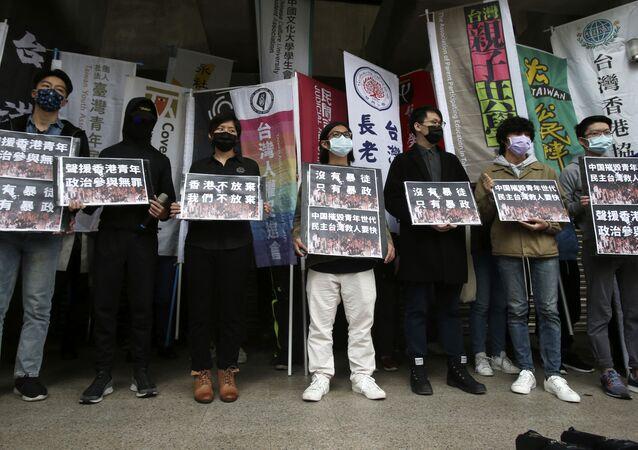 Manifestantes de Hong Kong que vivem em Taiwan seguram cartazes com mensagem escrita Solidariedade com a juventude de Hong Kong. Participação Política não é culpável