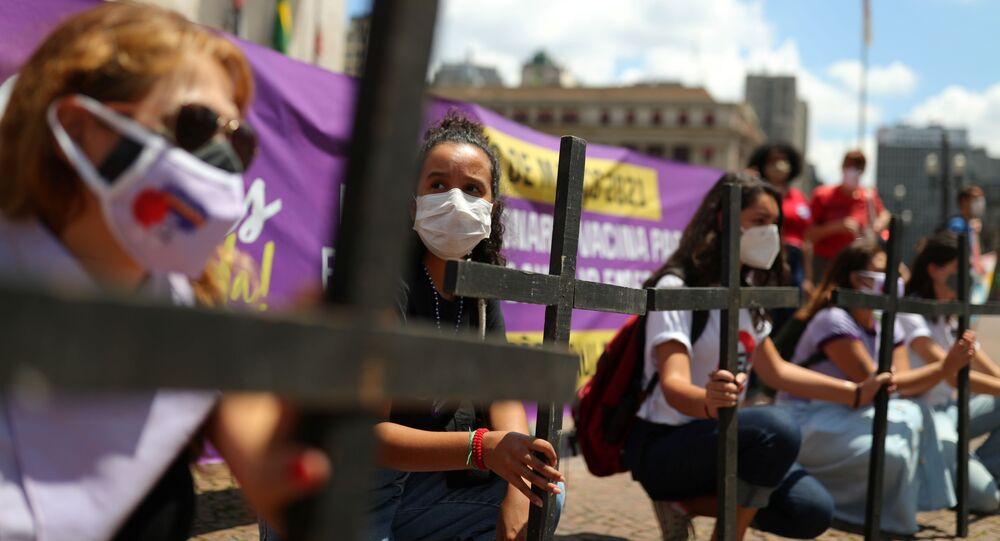 Mulheres seguram cruzes durante protesto contra a resposta do presidente Jair Bolsonaro à pandemia de COVID-19, em São Paulo, 8 de março de 2021