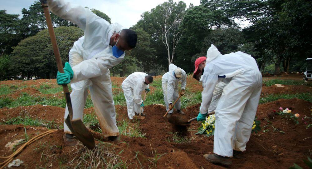 Funcionários de cemitério em São Paulo sepultam vítima da COVID-19.