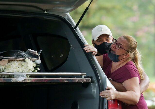 Parente reage durante enterro de vítima da COVID-19 no cemitério da Vila Formosa, São Paulo, 9 de março de 2021