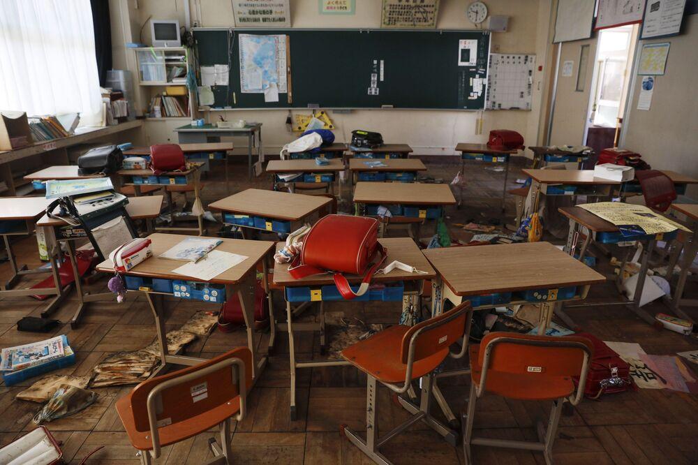 Sala de aula de escola primária abandonada cheia de mochilas escolares e outras coisas de alunos deixadas para trás durante evacuações após terremoto de 2011, em Futaba, prefeitura de Fukushima, Japão, 3 de dezembro de 2019