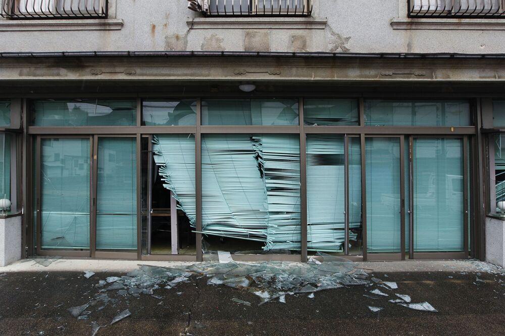 Vidros quebrados de portas de uma loja após terremoto, deixados intocados, na rua principal da cidade de Tomioka, prefeitura de Fukushima, Japão, 19 de agosto de 2011