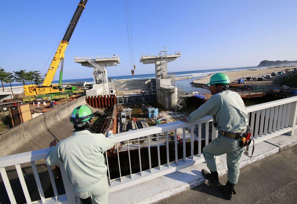 Trabalhadores olham para uma comporta em construção após alerta de tsunami ser emitido, em Iwaki, prefeitura de Fukushima, Japão, 22 de novembro de 2016
