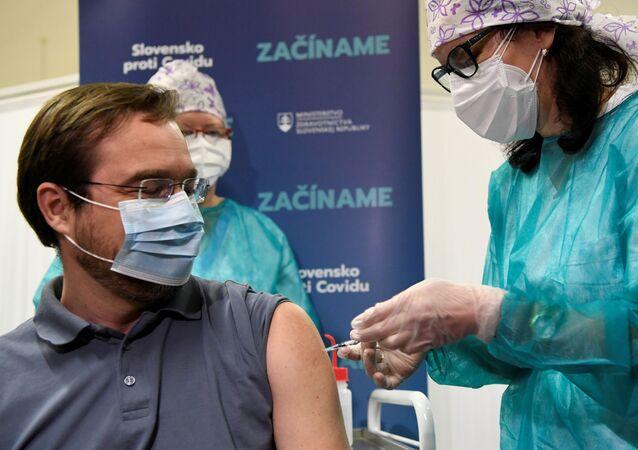 Marek Krajci, ministro da Saúde da Eslováquia, recebe dose da vacina Pfizer/BioNTech contra a COVID-19 no Hospital Universitário, Nitra, Eslováquia, 26 de dezembro de 2020