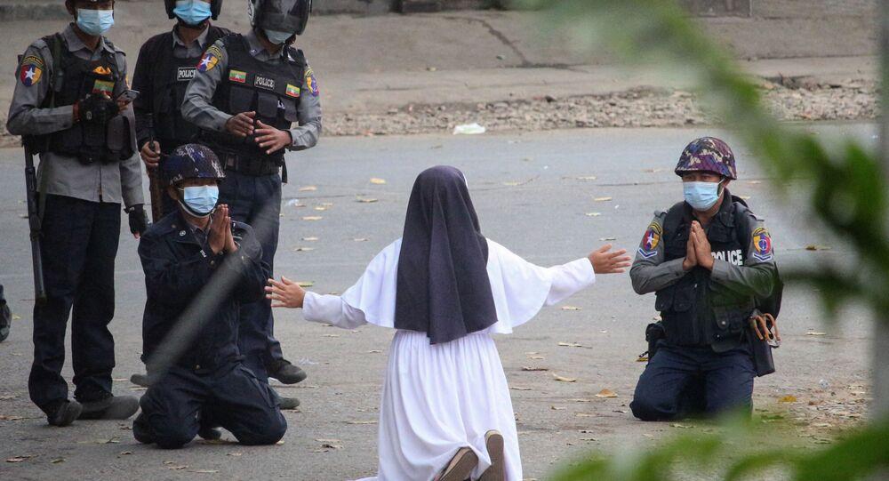 Freira ajoelhada pede à polícia para não machucar os manifestantes contra o golpe militar em Mianmar