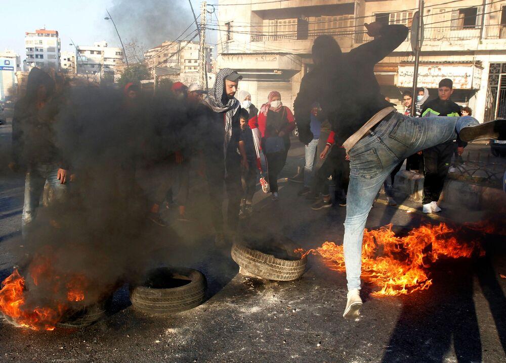 Manifestantes bloqueiam estrada com pneus incendiados durante uma ação de protesto contra a queda da libra libanesa em Sidon, Líbano