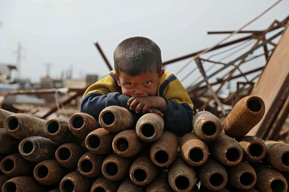 Criança debruçada sobre monte de projéteis desativados na cidade de Maaret Misrin, Síria