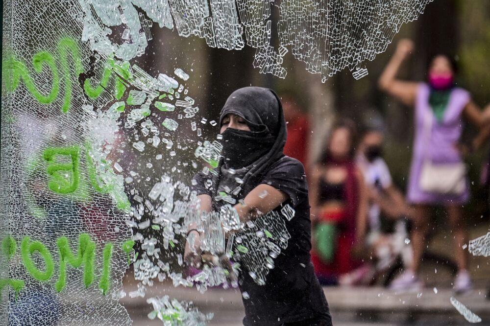 Mulher quebrando vidro durante manifestação no Dia Internacional da Mulher, na Cidade do México