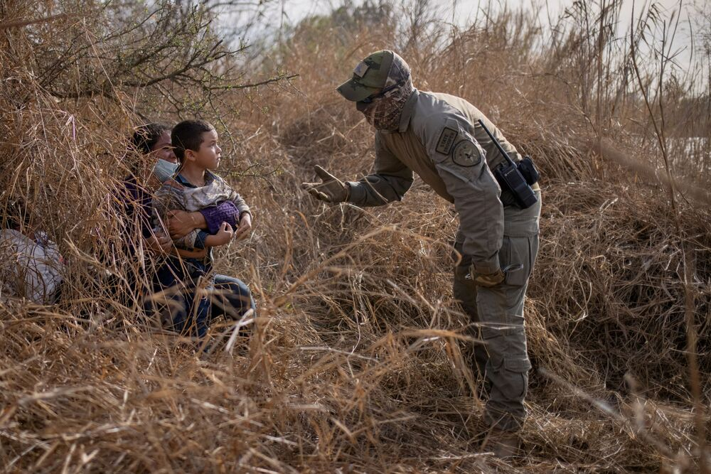 Agente de segurança do estado do Texas falando com migrantes
