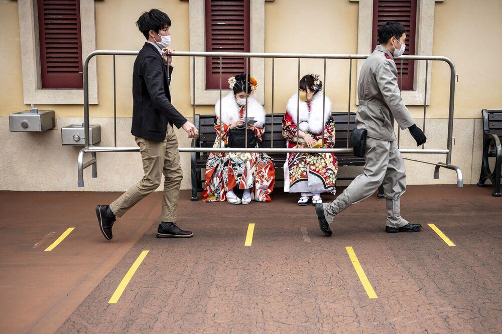 Jovens japonesas sentadas na rua em quimono
