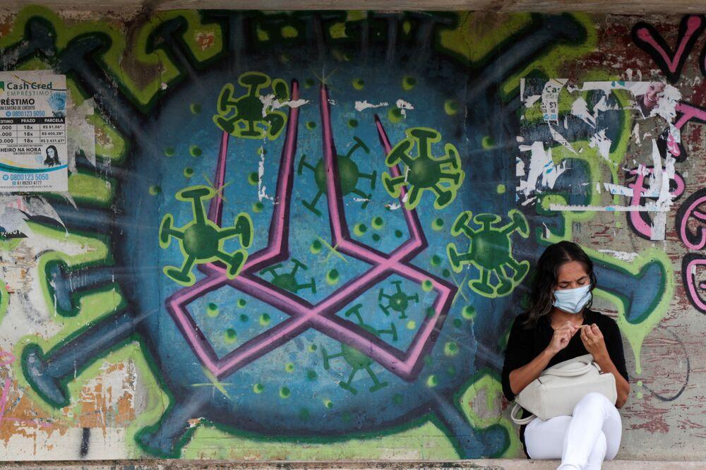 Mulher sentada em frente a um grafite retratando coronavírus, Brasília, 11 de março de 2021