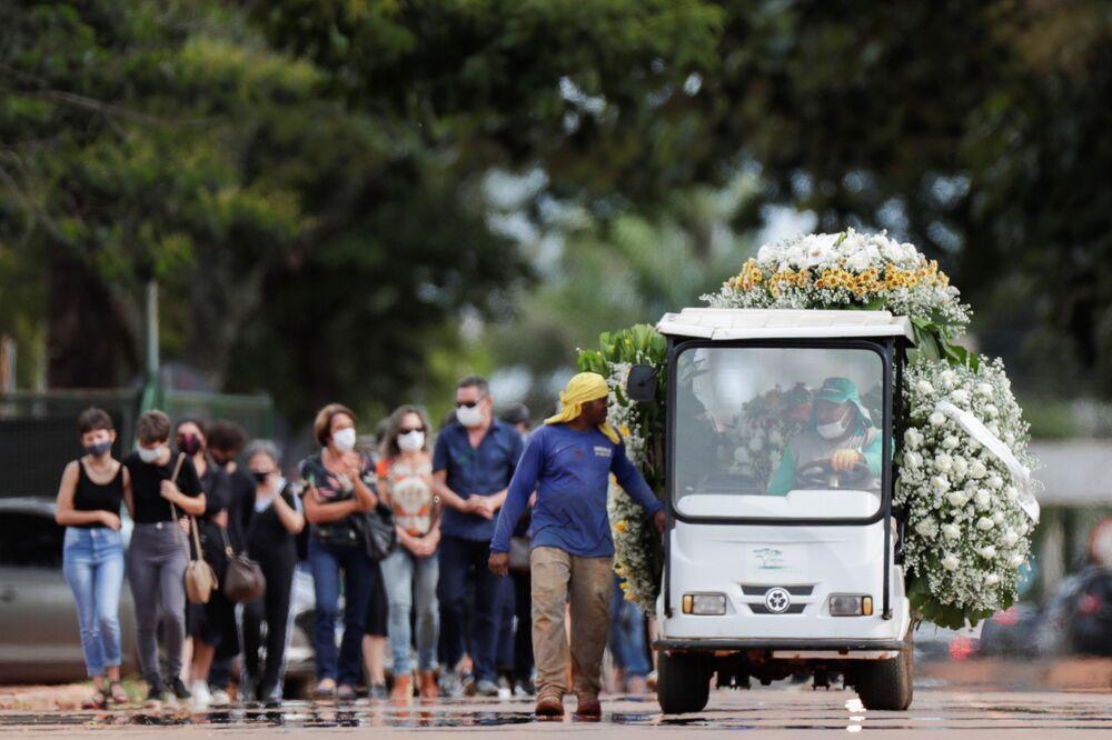 Funcionário transportando flores e caixão de pessoa falecida pelo coronavírus no Cemitério Campo da Esperança, 11 de março de 2021, Brasília