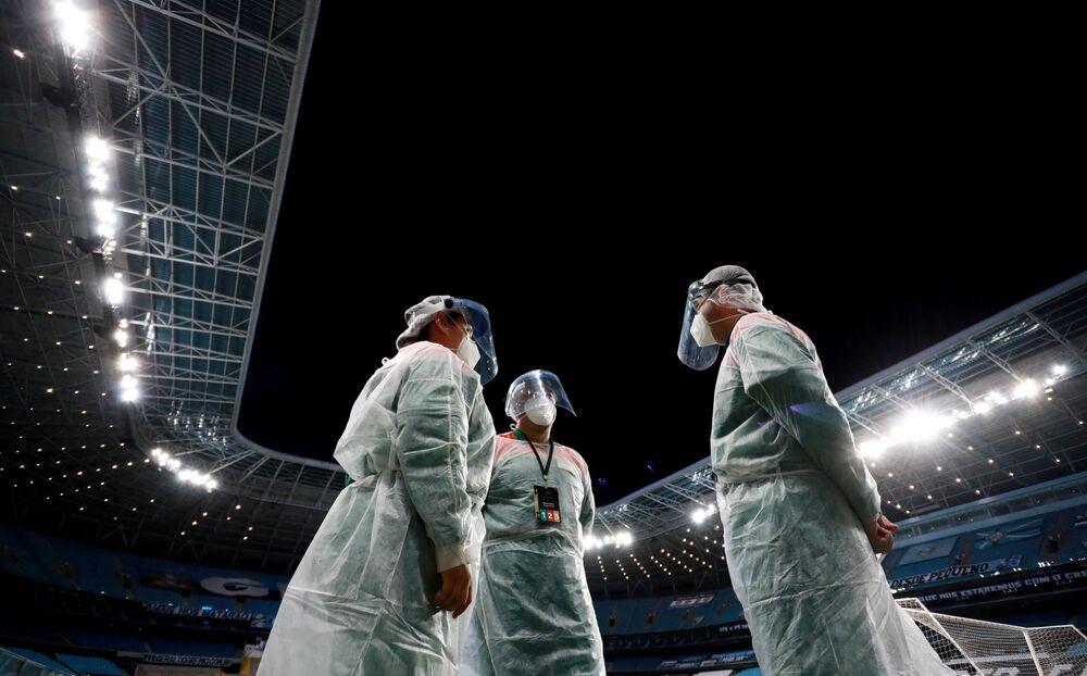 Funcionários da Arena do Grêmio em Porto Alegre vestindo trajes de proteção durante qualificação da Copa Libertadores, 11 de março de 2021
