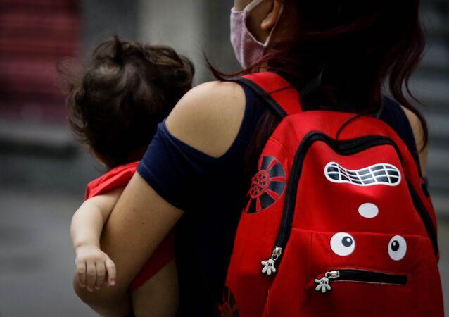 Criança é vista no colo da mãe em rua da cidade de São Paulo.