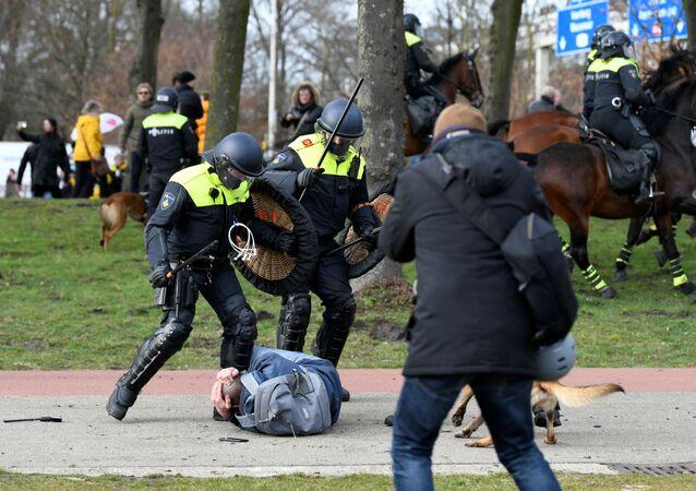 Polícia luta com um manifestante durante protesto contra as restrições para conter a COVID-19 em Haia, Países Baixos, 14 de março de 2021.