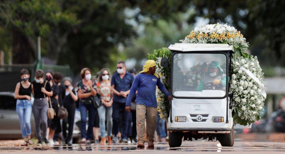 Carro com flores em enterro, no cemitério Campo da Esperança, em Brasília, de pessoa morta pela COVID-19